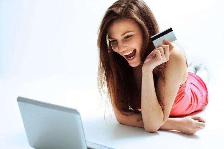 Девушка с кредиткой улыбается