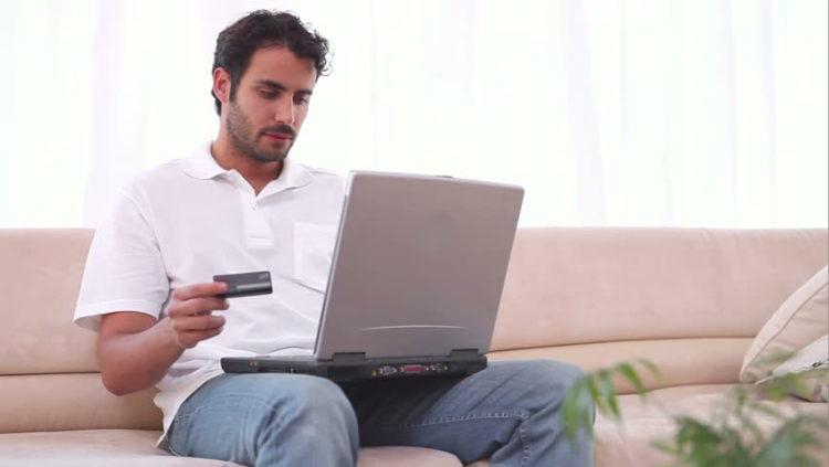 парень с банковской картой и ноутбуком