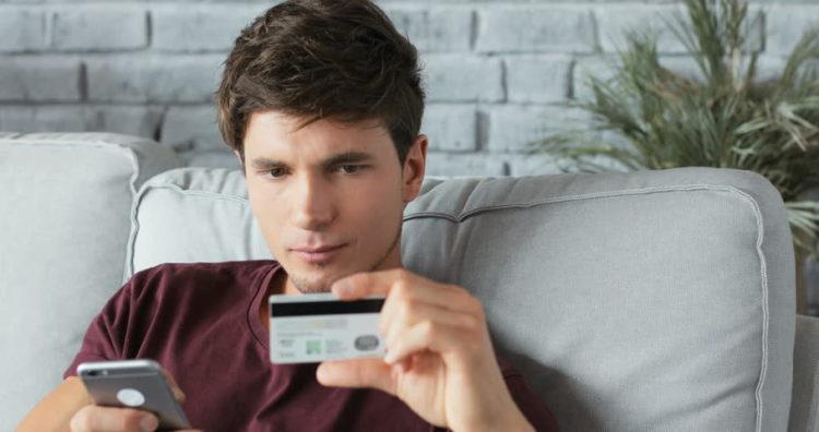 парень смотрит на банковскую карту